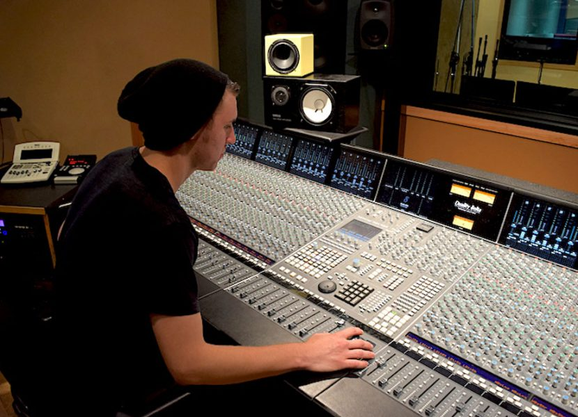 Picture of person in studio at the audio booth, while recording and producing music